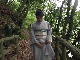 Amazingly spectacular JAV milf Akemi Horiuchi in a enrobe flashes her not worth multitude while outdoors in a forest at the kneeling to perform a blowjob in HD regarding English subtitles